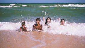 说谎在海滩的四个孩子在海浪 影视素材