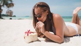说谎在海滩的妇女喝从椰子和看直接照相机 股票视频
