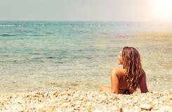 说谎在海滩的美丽的少妇在日落 免版税库存照片