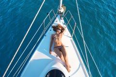 说谎在游艇甲板的女孩 免版税库存照片