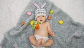 说谎在灰色毯子的兔宝宝帽子的女婴用多彩多姿的复活节彩蛋 库存图片