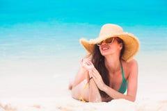 说谎在热带海滩的比基尼泳装和草帽的妇女 免版税库存图片
