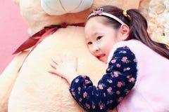 说谎在玩具的逗人喜爱的亚裔矮小的美丽的女孩 免版税库存照片