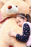 说谎在玩具的逗人喜爱的亚裔矮小的美丽的女孩 免版税库存图片