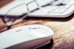说谎在玻璃和白色键盘旁边的白色计算机老鼠在木表上 免版税库存图片