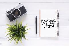 说谎在白色木背景的运转的书桌和照相机平的位置视图照片有新年目标书法笔记本的 库存图片