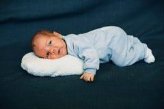 说谎在白色长毛绒枕头的新出生的男婴 免版税库存图片