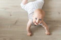 说谎在硬木和微笑的逗人喜爱的矮小的男婴 爬行在木木条地板和查寻与愉快的面孔的孩子 从a的看法 免版税库存图片