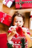 说谎在礼物中的地板上的小女孩 免版税库存图片