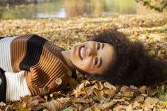 说谎在秋季叶子的年轻美国黑人的妇女在晴朗的公园 免版税库存照片