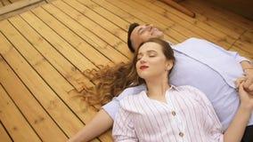 说谎在移动的船甲板的年轻夫妇在夏日 有长的深色的头发的女孩在白色,旅行在温暖的小船 股票视频