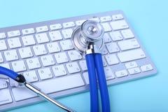 说谎在笔记本键盘和绿色玻璃的一个蓝色听诊器的特写镜头 选择聚焦 免版税图库摄影