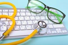 说谎在笔记本键盘和绿色玻璃的一个黄色听诊器的特写镜头 选择聚焦 免版税库存图片