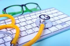 说谎在笔记本键盘和绿色玻璃的一个黄色听诊器的特写镜头 选择聚焦 免版税库存照片