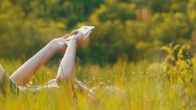 说谎在绿色草坪的愉快的少妇使用在风景领域的智能手机在日落背景 影视素材