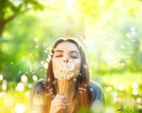 说谎在绿草和吹的蒲公英的美丽的少妇 免版税图库摄影