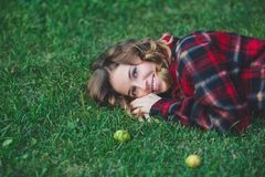 说谎在绿草的一件男性法绒衬衣的美丽的少妇 库存照片