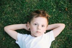 说谎在绿草的美丽的沉思孩子 免版税图库摄影