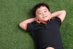 说谎在绿草的逗人喜爱的小男孩在公园 免版税图库摄影