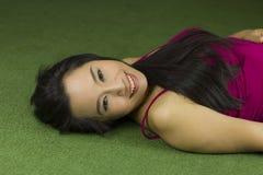 说谎在绿草,一名美丽和梦想的泰国妇女的亚裔妇女放下在绿草,放松,当看时 免版税图库摄影
