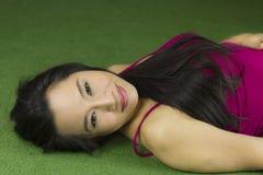 说谎在绿草,一名美丽和梦想的泰国妇女的妇女放下在绿草,放松,当看照相机时 免版税库存照片