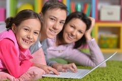 说谎在膝上型计算机前面的地板上的幸福家庭 免版税图库摄影