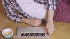 说谎在膝上型计算机键盘的木地板键入的文本的一个人的特写镜头 影视素材