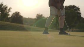 说谎在草在阳光下光芒的高尔夫球 移动与高尔夫俱乐部的未被认出的成熟人球 E 股票录像