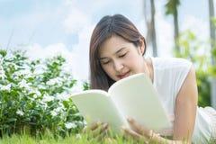 说谎在草地的亚裔妇女为在公园读了一本白皮书,由美丽的亚裔妇女的放松概念 免版税库存图片