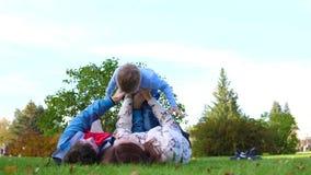 说谎在草坪的愉快的家庭 拿着他的他的胳膊的母亲和父亲儿子在他的头,孩子微笑 在 影视素材