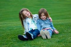 说谎在草甸的两个朋友女孩 免版税库存照片
