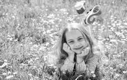 说谎在草的女孩在grassplot,绿色背景,拷贝空间 微笑的面孔的女孩花费休闲户外 全盛时期 库存照片