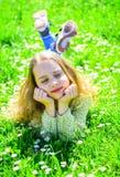 说谎在草的女孩在grassplot,绿色背景 孩子享受春天晴朗的天气,当说谎在草甸时 女孩 库存图片