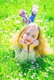 说谎在草的女孩在grassplot,绿色背景 孩子享受春天晴朗的天气,当说谎在草甸时 ?? 库存图片