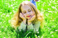 说谎在草的女孩在grassplot,绿色背景 梦想的面孔的女孩花费休闲户外 全盛时期概念 孩子 库存图片