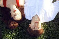 说谎在草的年轻人浪漫夫妇在公园 放松与眼睛的愉快的夫妇关闭了 有红色嘴唇的女孩 ?? 免版税图库摄影