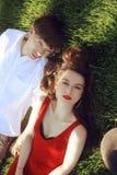 说谎在草的年轻人浪漫夫妇在公园 放松在绿草的愉快的夫妇 ?? 一件美丽的礼服的一个女孩 免版税库存图片
