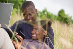 说谎在草的愉快的夫妇在夏天 免版税图库摄影