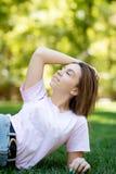 说谎在草的美丽的微笑的妇女室外 她是绝对愉快的 生活方式,暑假 免版税库存照片