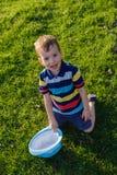 说谎在草的英俊的小男孩 小梦想家在有帽子的草甸在 孩子本质上在城市之外的 无忧无虑的假期 免版税库存照片
