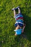说谎在草的英俊的小男孩 小梦想家在有帽子的草甸在 孩子本质上在城市之外的 无忧无虑的假期 免版税库存图片