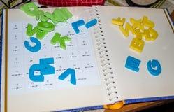 说谎在被打开的书的塑料字母表 免版税库存照片