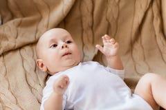 说谎在被编织的毯子的甜矮小的男婴 免版税库存照片