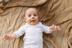 说谎在被编织的毯子的甜矮小的男婴 库存照片