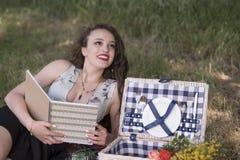 说谎在野餐桌布和读书的年轻美丽的妇女 免版税库存照片