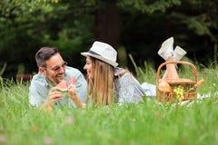 说谎在野餐毯子的年轻夫妇,吃水梅隆和放松 免版税库存图片