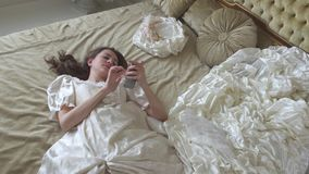 说谎在金子装饰的床上和发短信在手机关闭的舞会礼服的年轻疲乏的妇女  股票录像