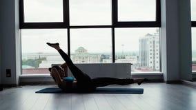 说谎在锻炼席子的灵活的年轻女人和提起她的腿慢动作 影视素材