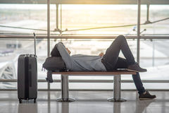 说谎在长凳的年轻亚裔人在机场终端 库存图片