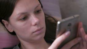 说谎在长沙发和读某事的哀伤的妇女在手机 接近的装饰表面留给嘴唇桃红色结构树 股票视频